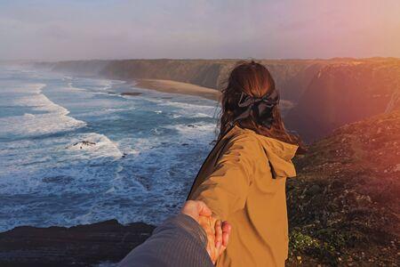 Mujer joven con primer plano de la mano masculina cerca de la costa del océano.