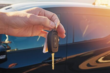 Mans hand holding a key from the car close-up