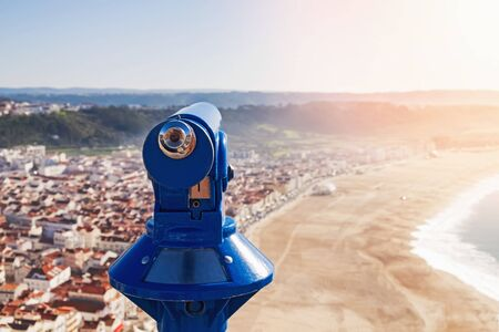 Touristic binocular telescope looking on the city and beach. Banque d'images