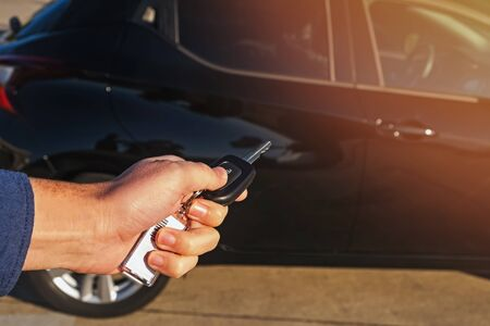 Man's hand close-up pushing button on remote control car key Stock Photo