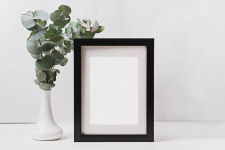 Frame with empty paper and eucalyptus branches in the vase. Poste mock-up. Empty place for text or picture