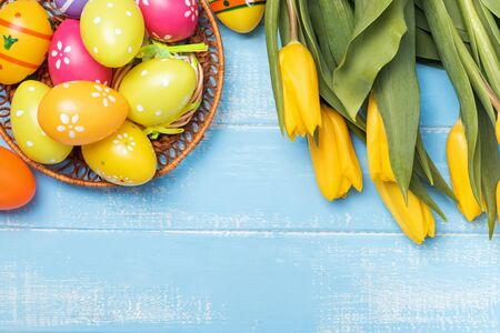 Decorative eggs and yellow tulips on blue wooden background, top view. Happy easter. 版權商用圖片