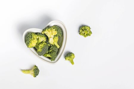 Fresh broccoli in a heart shaped bowl on white background