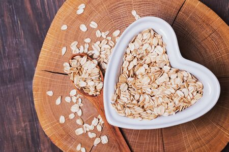 Oatmeal in heart shaped plate on wooden surface