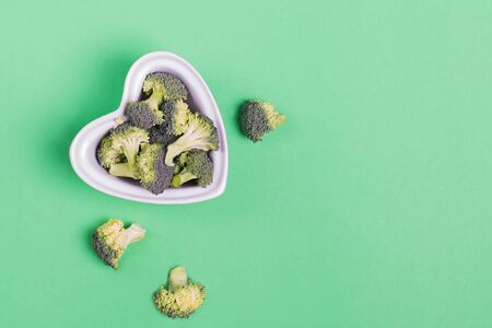 Fresh broccoli in a heart shaped bowl on green background,