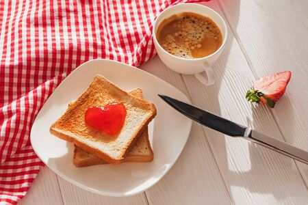 Toasted bread slices with jam in heart shape on it and cup of coffee in natural morning light. Delicious breakfast concept. 写真素材
