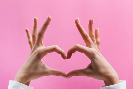 Feminine hands forming a heart symbol on pink background close-up
