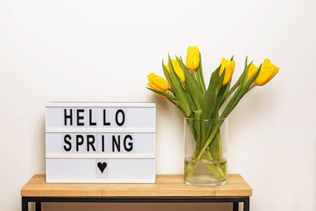 Hello Spring text on a display lightbox with yellow tulips in a vase standing near the white wall
