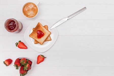 Breakfast with toasted bread and jam in heart shape, strawberries and coffee on the white table, top view