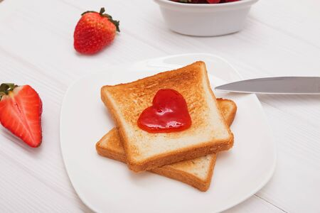 Toasted bread with jam in heart shape and strawberries on the white table. Delicious breakfast close-up