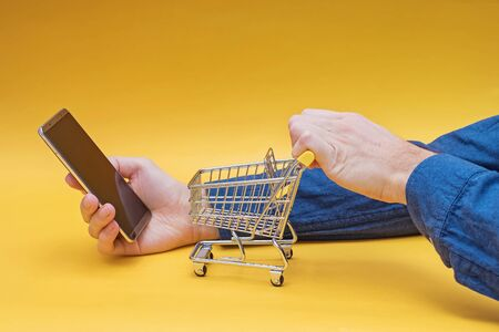 Hands holding mini shopping trolley and smartphone on yellow background. Online supermarket, food delivery app concept.