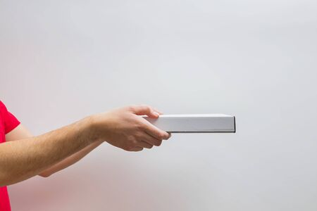 Male hands holding a box with pizza against the white wall with copy space.