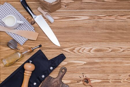 Kitchen utensils and accessories on wooden table with copy space.