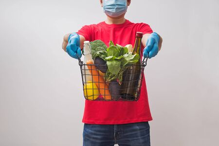 Delivery man wearing mask and gloves holding craft paper box full of different groceries.