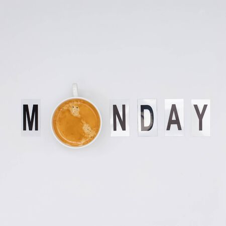 Cup of coffee as letter O in word Monday arranged from print letters