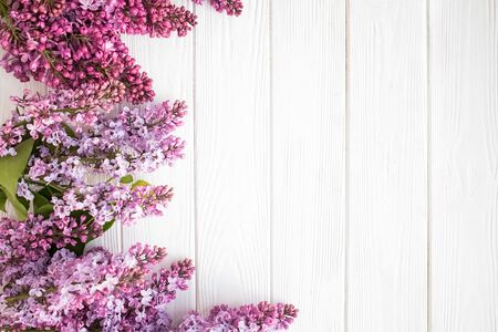 Lilac flowers on white wooden background.