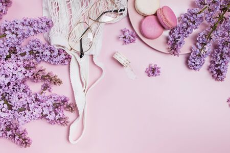 Spring flat lay with lilac flowers, glasses and macarons