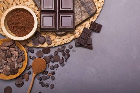 Chocolate pieces and drops, cocoa beans and powder on grey background Stock Photo