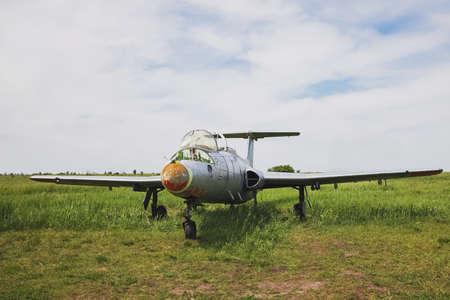 Lonely abandoned vintage jet plane on green meadow