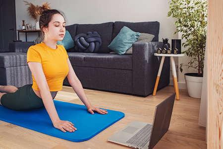 Young woman doing yoga at living room