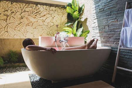 Man lying in bathtub full of flower petals.
