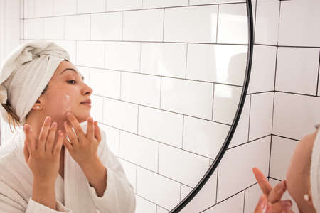 Young woman applying moisturizer cream on face standing in the bathroom Imagens