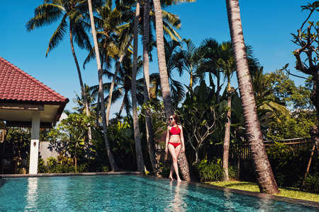 Young woman in red swimsuit standing neat the beautiful swiming pool