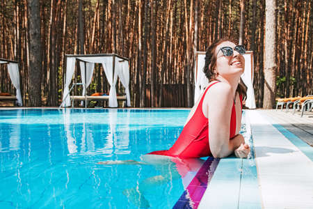 Woman in red swimsuit relaxing in swimming pool