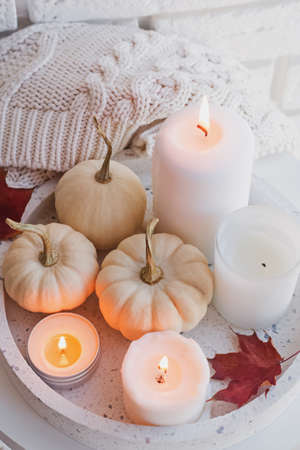 Autumn still life with white pumpkins and burning candles
