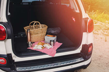 Picnic Package and Basket with Croissant and Sandwiches Lies on the in the trunk of hatchback car Stockfoto