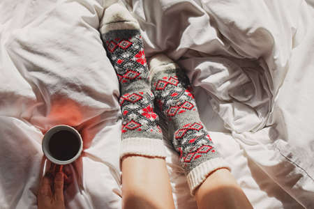 A cup of coffee or tea and female feet in warm knitted socks
