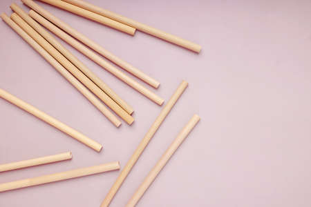 Reusable bamboo straws on the pink background,