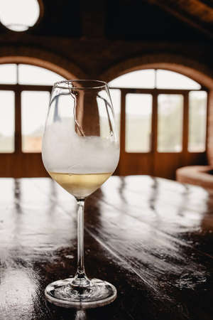 A glass of white wine on rustic wooden table
