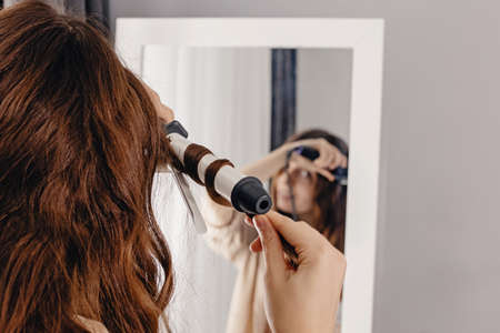 Young woman styling her shiny long brown hair