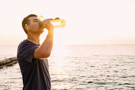 Young male runner drinking water from the bottle after the jogging