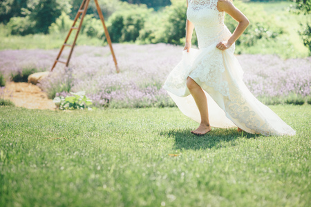 woman is running on the grass in wedding dress sunny day Stock Photo