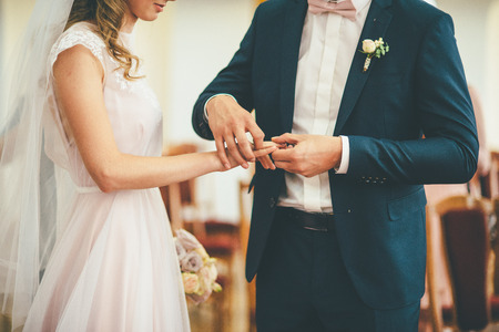 Ceremony of putting on a wedding rings. Boy in suit and girl in chiffon wedding dress