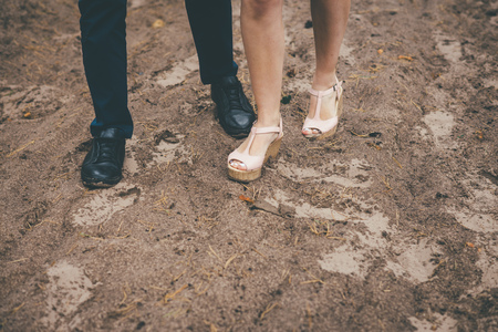 Newly married couple walking in the forest legs and shoes closeup, bride and groom together
