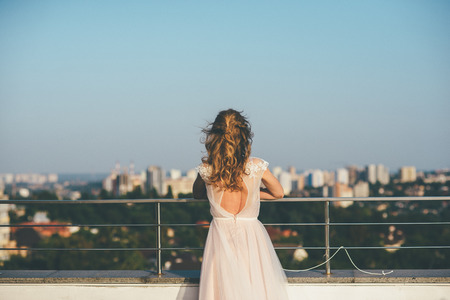 Gorgeous woman in wedding white dress faces the city of Kyiv, with hands resting on steel railings and beautiful curly hairstyle. 免版税图像
