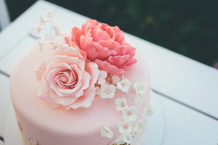 Pink glazed cake with flowers on top for wedding stands. Delicious sugary decoration for wedding. Green blurred bushes on background.