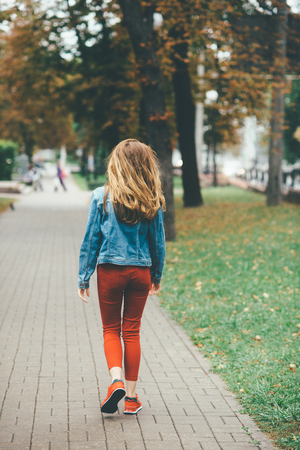 Blonde young girl in red jeans and denim coat walks in autumn gold park 스톡 콘텐츠