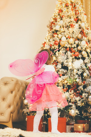 Back view of the pretty little girl with toy pink wings, blurred Christmas tree as a background