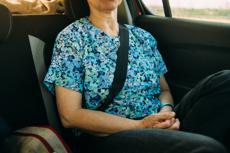 woman is travelling in the car with safety belt on the back sit Reklamní fotografie