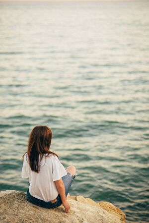 Beautiful young woman sits on the beach, dreaming and looking at the sea. A look from the back, against the background of sea and ocean waves on the sunset