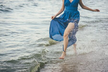 Lady in a blue dress running along the water's edge. She running barefoot on the water and splashes spreads from her feet. The hem of her dress is wet with water. No face visible.