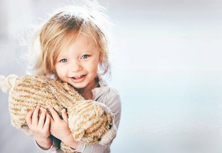 Close up shot of a nice blonde blue eyed girl holding a plush toy in her hand and smiling innocently copy space