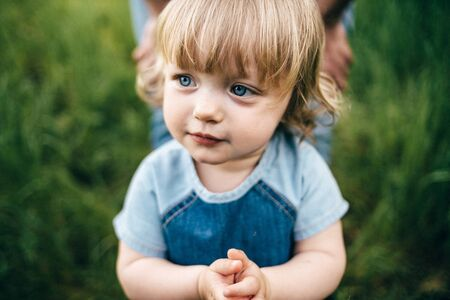 Child outdoors in nature. Happy girl. Funny baby girl isolated on a background of green trees. Portrait of cute kid girl. Happy kid holding hands in jeans dress close up