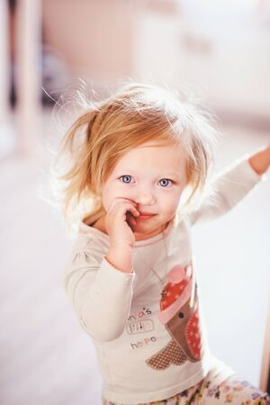Beautiful child with light hair and deep blue eyes innocently plays with her hands Standard-Bild