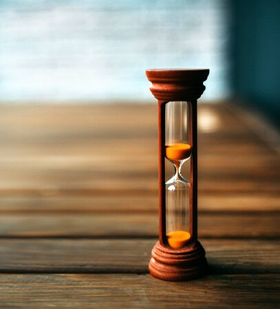 Hourglass closeup stand on a wooden floor. In the background is a light blue brick wall. photo from the room. Timing Time does not stand still.