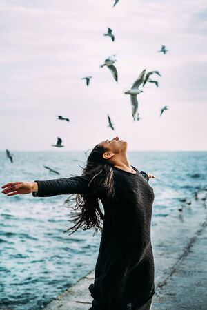 Close-up A young girl in black clothes is standing by the sea with a strong wind. seagulls fly. The power of thought, magic, self-awareness, gaining strength to overcome difficulties. Mental health